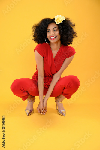 Young African American Woman in Red Jumpsuit Squatting Down