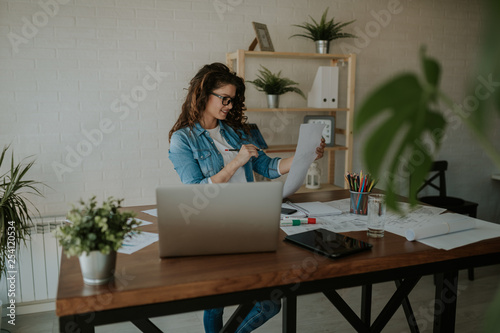 Young entrepreneur woman, sitting at office desk, with laptop, plants, papers on it. Holding a paper, finishing work.