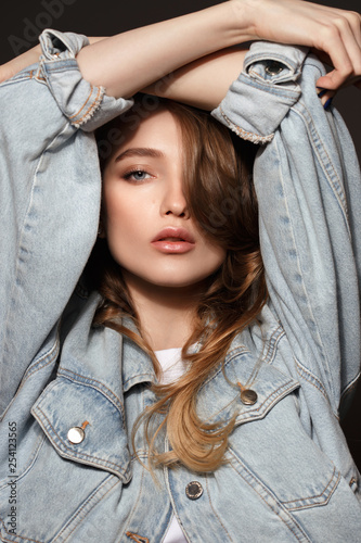 Young brunette girl with long flowing hair dressed in jeans jacket poses holding her hands on her head on the dark background in the studio