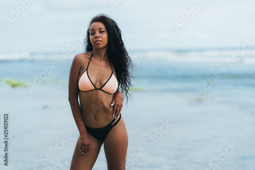Leinwandbild Motiv Sexy african american girl in swimwear resting on ocean beach. Young black skinned woman with curly hair stands on seashore