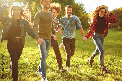 Cheerful friends are running in the park. © Studio Romantic