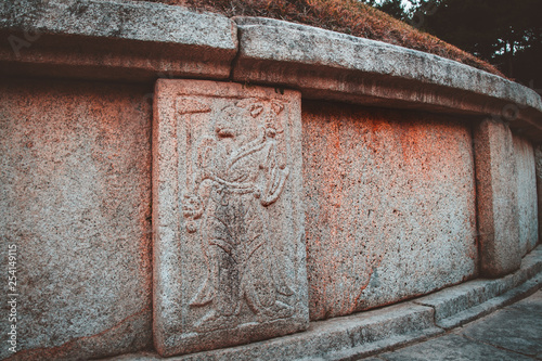 Relief carvings of Oriental zodiac god, half man, half animal, standing guard around the tomb of General Kim Yusin in Gyeongju, South Korea. Known as the Hero of the Silla Kingdom © tanaonte