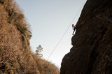 Girl equipped with a rope climbing on the sloping rock and looking up