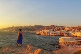 Attractive young woman with blue dress is overlooking Little Venice on Mykonos island, Greece