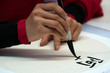 japanese woman writing ideograms with brush