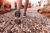 feet in sneakers on a rocky road