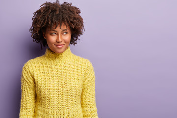 Headshot of curious satisfied dark skinned woman with curly haircut, looks away with intention or intriguing plan, wears yellow clothes, has something in mind, poses against purple wall, blank space © Wayhome Studio