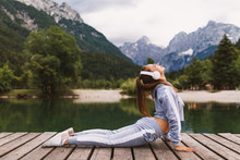 """Постер, картина, фотообои """"Young sports woman stretching at dock on the lake in the mountains"""""""
