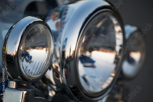 Leinwanddruck Bild Chromed motorcycle headlights close up