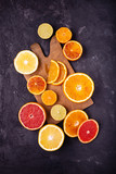 Various types of citrus fruit cut into slices on a dark background