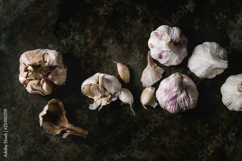 Group of fresh organic garlic bulbs clove whole and peeled over dark metal background. Flat lay, space