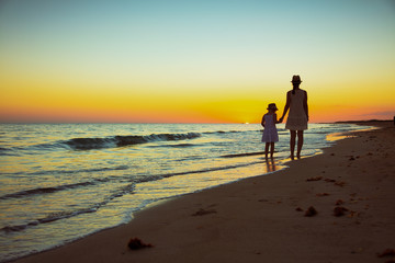 mother and daughter tourists on ocean coast at sunset walking © Alliance