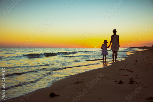 mother and daughter tourists on ocean coast at sunset walking