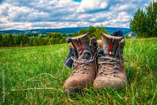 Leinwandbild Motiv Wandern in Deutschland: Gebrauchte Wanderschuhe im Gras