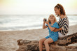 mother and child sitting on a wooden snag and taking photos with