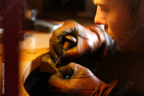 Jeweler engraving the ring with sharp with an awl in a workshop lith with warm light © briagin