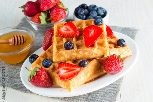 Photo of fresh homemade food made of berry Belgian waffles with honey, chocolate, strawberry, blueberry, maple syrup and cream. Healthy dessert breakfast concept with juice.  - 254232734