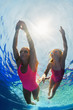 Leinwanddruck Bild - Happy family - young mother, girl learn to swim and dive underwater. Jump with fun in swimming pool. Healthy lifestyle, active parents, people water sports activities on summer holidays with kids.
