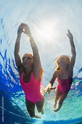 Leinwanddruck Bild Happy family - young mother, girl learn to swim and dive underwater. Jump with fun in swimming pool. Healthy lifestyle, active parents, people water sports activities on summer holidays with kids.