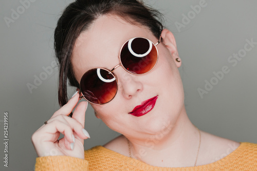 young woman close up portrait with sunglasses smiling. led ring reflection in the eyes. Real woman concept