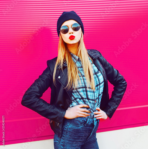 Fashion portrait blonde cool girl sending sweet air kiss posing in rock black style jacket, hat posing on city street over colorful pink wall background