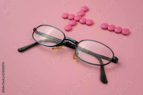 Glasses with plus and minus made of pills on pink background. Concept of eyesight correction