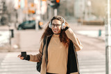 Mixed race teenage having headphones and listening music while standing on the street.