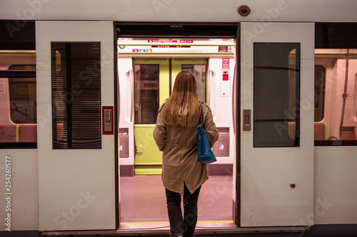 Rear View Of Young Woman Waiting For Subway.  Entering Train.