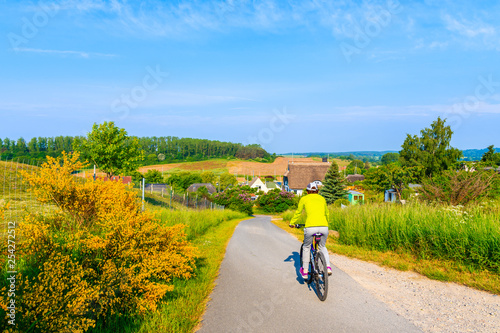 obraz lub plakat Young woman riding bicycle along green fields to sailing port of Seedorf, Baltic Sea, Germany