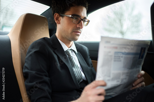 Leinwanddruck Bild Young manager reading a newspaper in the back seat of a car
