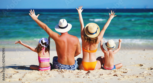 fototapeta na ścianę happy family father, mother and children backs on beach at sea.