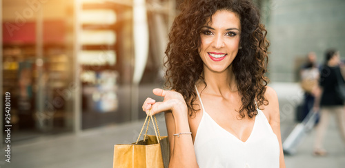 Beautiful woman holding a bag in a shopping mall - 254280119