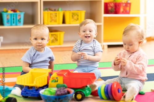 Leinwandbild Motiv Nursery babies girl and boys playing together in playroom in kindergarten