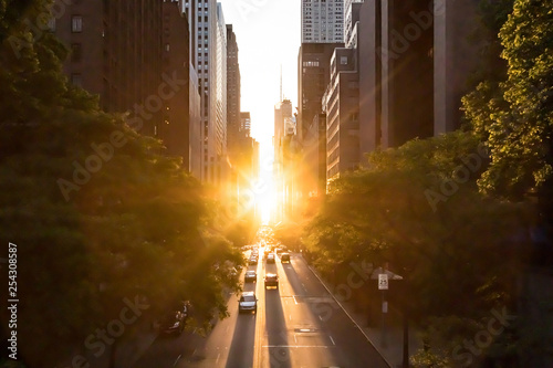 Sunlight shines on the buildings and cars along 42nd Street through Midtown Manhattan around the Manhattanhenge sunset in New York City © deberarr