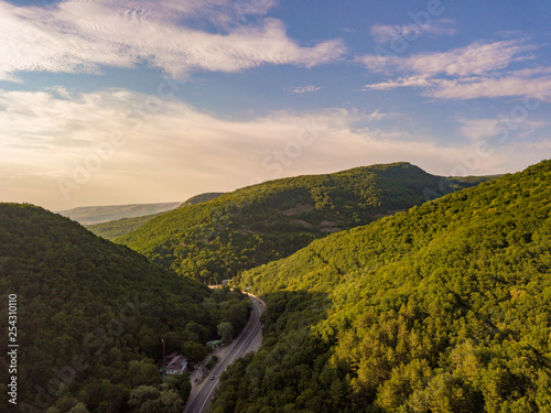 aerial view of wide highway between the mountains covered with green woods b