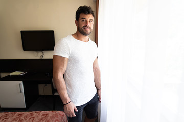 Young Man Standing Near Window in Hotel Room
