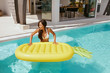 Summer vacation. Woman in swimsuit with float in swimming pool