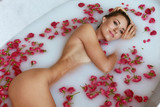 Spa. Woman in bath with milk and flowers enjoying body treatment