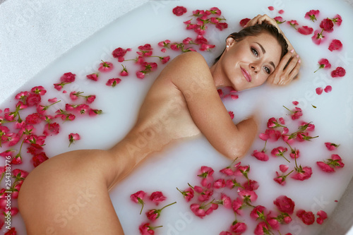 Leinwandbild Motiv Spa. Woman in bath with milk and flowers enjoying body treatment