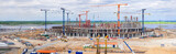 Fototapeta Na sufit - Panorama of the construction site of a huge stadium. Tower cranes, frame, monolithic floors, columns, construction camp and construction equipment, a huge number of workers. © ASP media