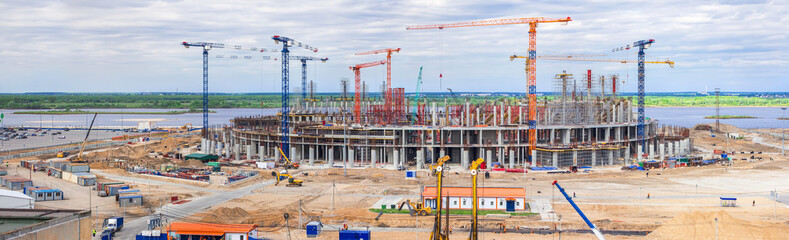 Panorama of the construction site of a huge stadium. Tower cranes, frame, monolithic floors, columns, construction camp and construction equipment, a huge number of workers.