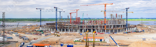 Panorama of the construction site of a huge stadium. Tower cranes, frame, monolithic floors, columns, construction camp and construction equipment, a huge number of workers. - 254321556
