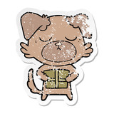 distressed sticker of a cute cartoon dog with christmas present