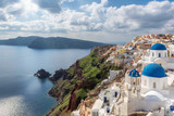 Traditional white houses and churches with blue domes over the Caldera, Santorini, Oia, Greece.