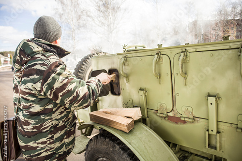 Military field kitchen. Vintage kitchen on the street. Cooking tea in the winter. Sunny day. Kindle the furnace and warming the water. © Олег Копьёв