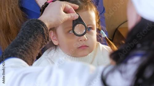 Professional ophthalmologist checks the eyesight of the child. Eye examination