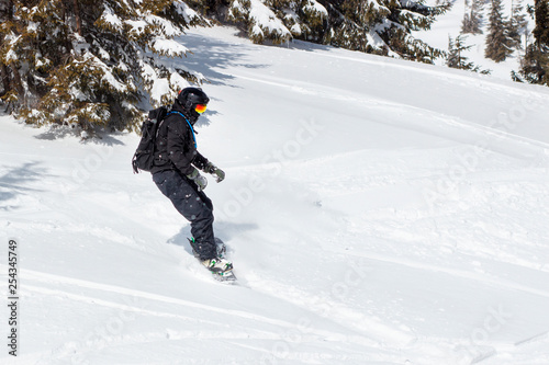 obraz lub plakat Young man snowboarder running down the slope in Alpine mountains. Winter sport and recreation, leisure outdoor activities.