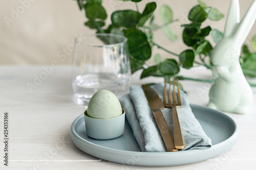 Leinwanddruck Bild Happy Easter concept. Close up of Easter  Egg in mint green plate with  napkin. Scandinavian style  background with copy space .