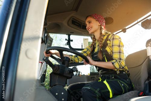 Leinwanddruck Bild Farmer woman driving a tractor