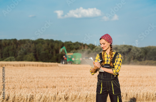 Leinwandbild Motiv Farmer woman monitoring business progress of the harvest